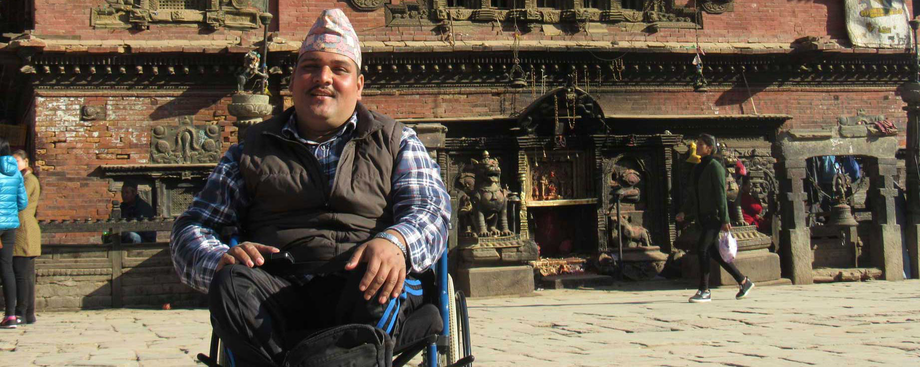A man in a wheelchair infront of traditional newari building.