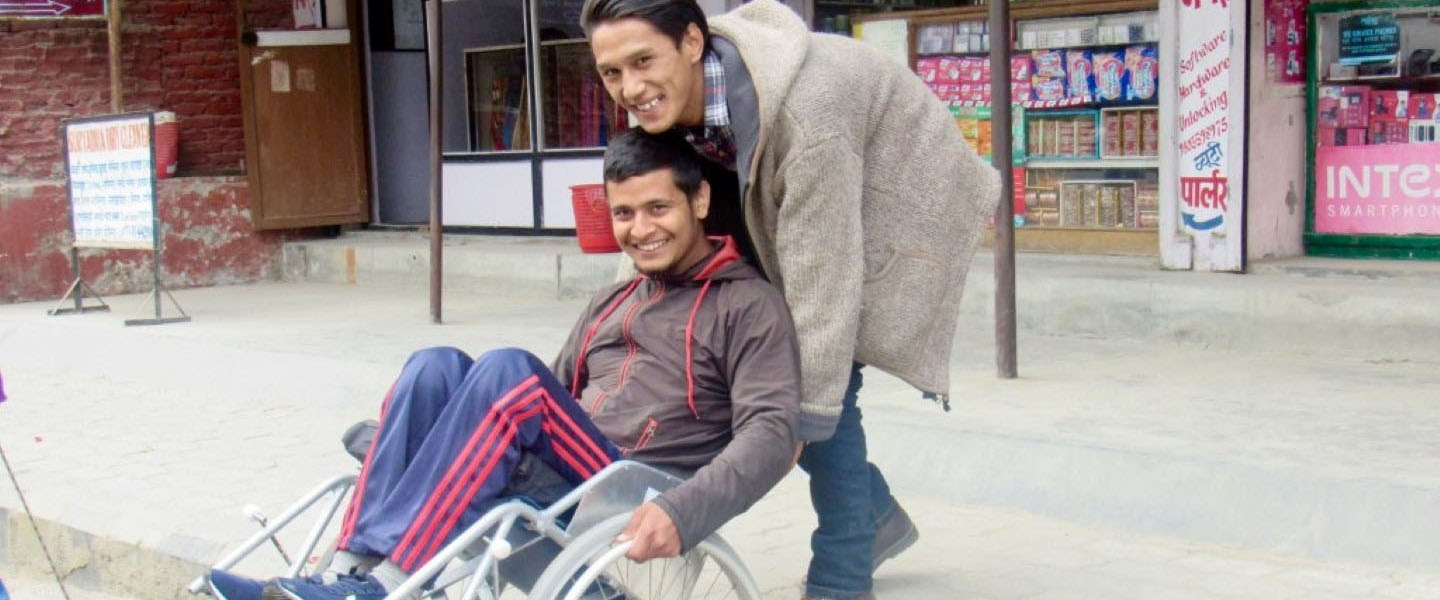 A wheelchair user is helped by an attendant to get down a curve