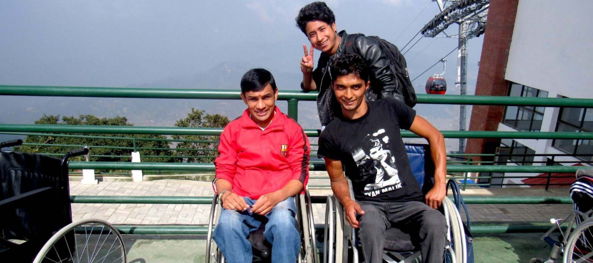 two persons with disabilities and a man standing behind him