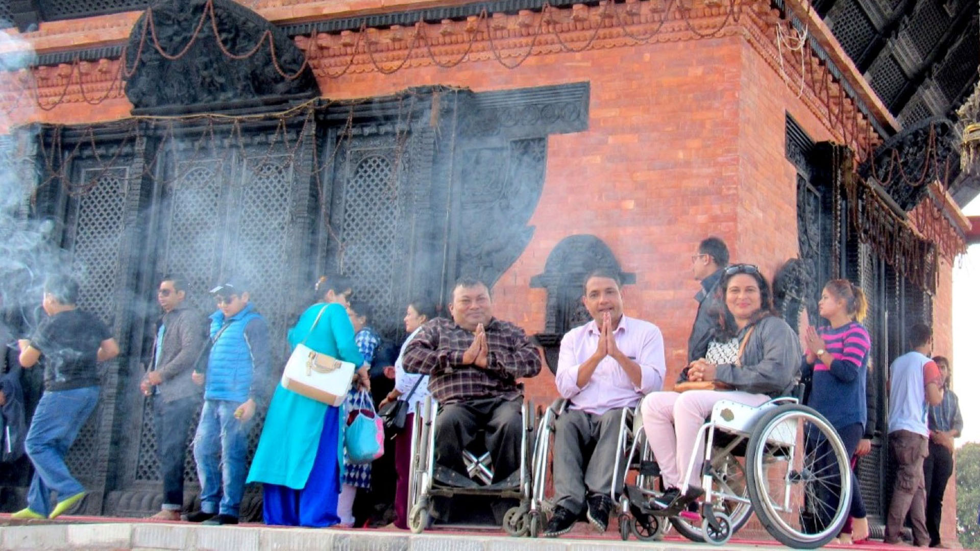 3 peresons in wheelchair infront of a temple
